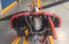 Motoren fra CS APA på værkstedet i Portugal. Der er to lydpotter, som sidder langt bagtil tæt på brandskottet. Som det fremgår er et der frit kik ind i potten til venstre - ved den røde pil - fordi et dæksel er faldet af. Dækslet på højre lydpotte er stadig på plads